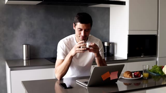 portrait of a handsome relaxed caucasian man in a white shirt sitting on kitchen in front him laptop and smartphone. guy sipping a black tea from transparent mug and peacefully smiling - gente serena video stock e b–roll
