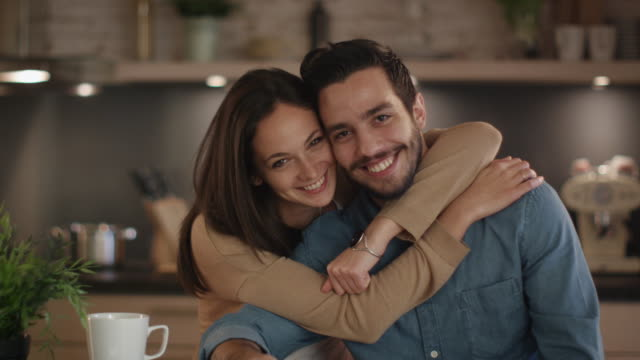 portrait of a handsome smiling couple in the kitchen. - couple portrait caucasian video stock e b–roll