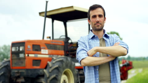 vídeos de stock e filmes b-roll de portrait of a handsome young farmer standing in a shirt and smiling at the camera, on a tractor and nature background. concept: bio ecology, clean environment, beautiful and healthy people, farmers. - agricultor