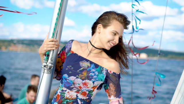 Portrait of a happy and young woman who is on a yacht, a boat sails by the sea on a warm day, the lady is happy and laughs, in her hands sunglasses video