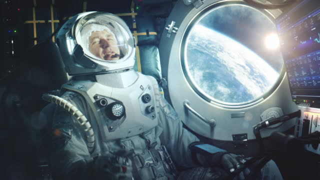 Portrait of a Happy Astronaut on a Space Ship In Orbit. Cosmonaut in a Futuristic Suit is Full of Joy and is Waving Hand on a Video Call. VFX Graphics Footage from the International Space Station.