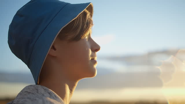 portrait of a happy boy in a hat looking at the beautiful blue sky, sun glare video