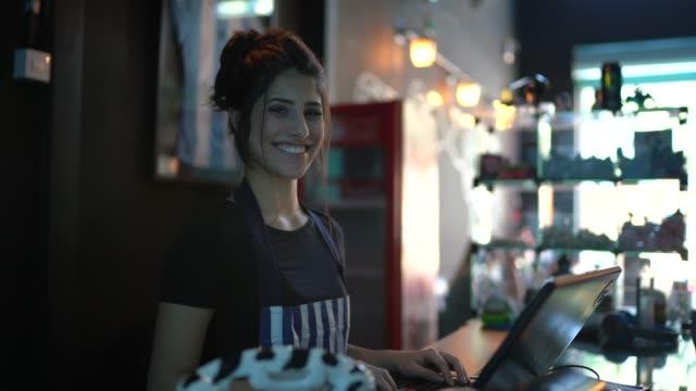 porträt einer glücklichen kassiererin, die in einer bar arbeitet - bedienungspersonal stock-videos und b-roll-filmmaterial