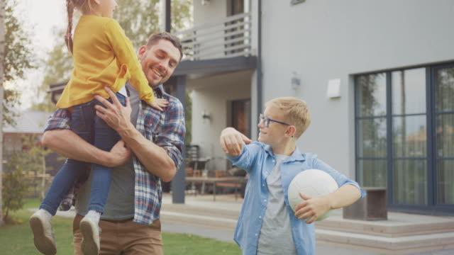 stockvideo's en b-roll-footage met portret van een gelukkig gezin van drie: vader, dochter, zoon. ze poseren voor de camera op een gazon naast hun landhuis. papa houdt het meisje in zijn armen. jongen houdt een voetbal. - garden house