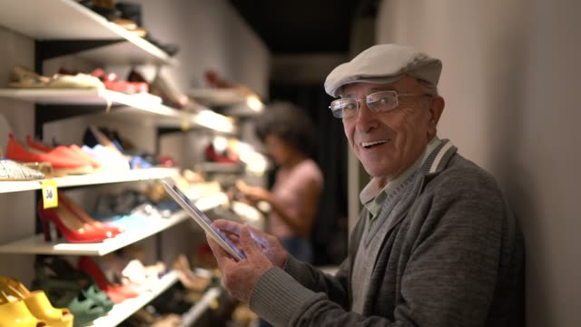 Portrait of a happy senior man using digital tablet in a shoe store video