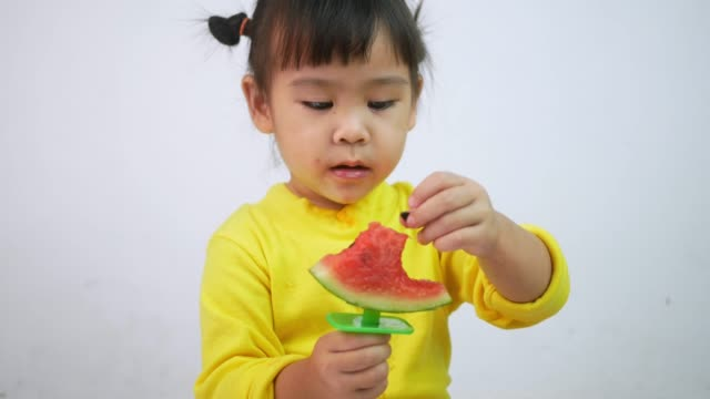 Portrait of a happy smiling Asian child girl and enjoy eating watermelon isolated on white background.