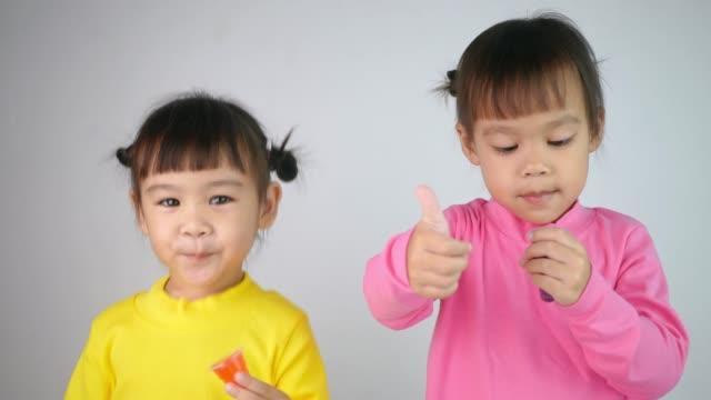 幸せな笑顔の兄弟の女の子の肖像画と白い背景に隔離ゼラチンデザートを食べることをお楽しみください。 - 兄弟姉妹点の映像素材/bロール