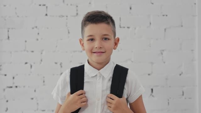 vidéos et rushes de portrait d'un élève heureux avec un prêt de sac à dos à l'école. retour à l'école. - fournitures scolaires