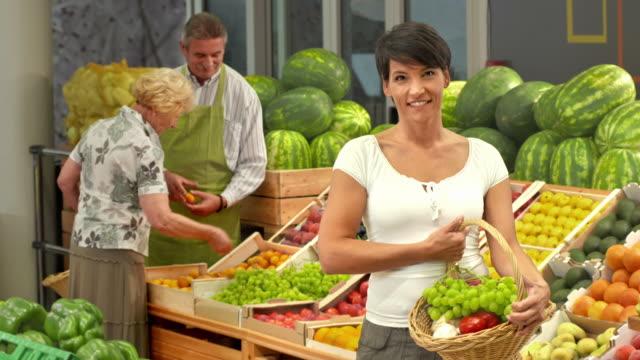 vídeos y material grabado en eventos de stock de hd: retrato de mujer feliz en una tienda de fruta y verdura - antioxidante