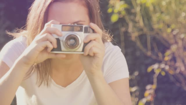 portrait of a happy young woman with retro camera smiling and taking photos - polaroid video stock e b–roll