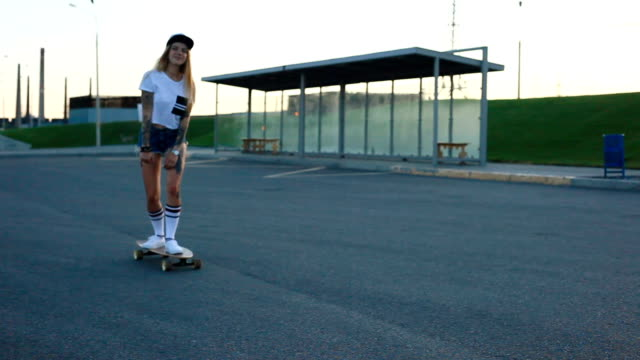 portrait of a hipster young girl smiling with a longboard at sunset. - funky video stock e b–roll