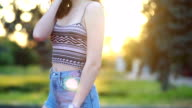 istock Portrait of a hipster young girl smiling with a skateboard at sunset. 1250138938