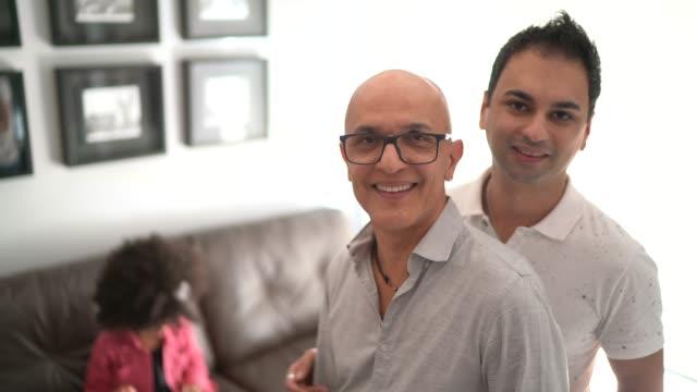 vídeos de stock, filmes e b-roll de retrato de um casal homossexual em casa - filha no fundo - lgbt