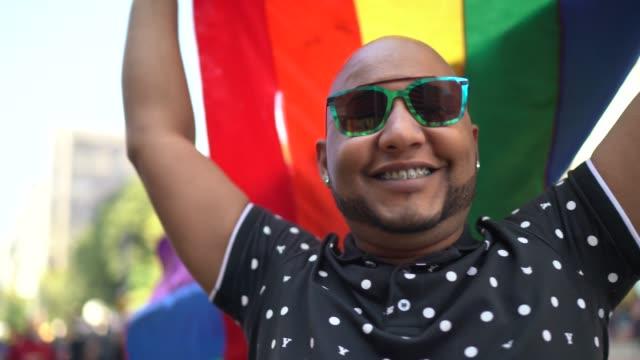 porträt eines lateinischen mannes, der während der lgbtqi-parade eine regenbogenflagge hält - gay man stock-videos und b-roll-filmmaterial