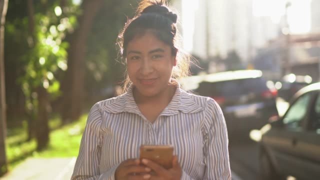 Portrait of a latin woman using cellphone in the street