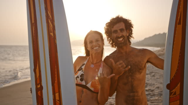 vídeos de stock e filmes b-roll de portrait of a laughing male and female surfer on the beach at sunset - tronco nu