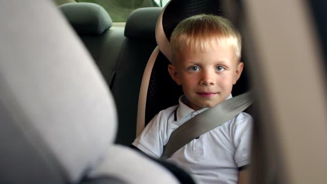 車のシートに乗った6歳の男の子の肖像画、彼はシートベルトを着ています。 - 安全点の映像素材/bロール