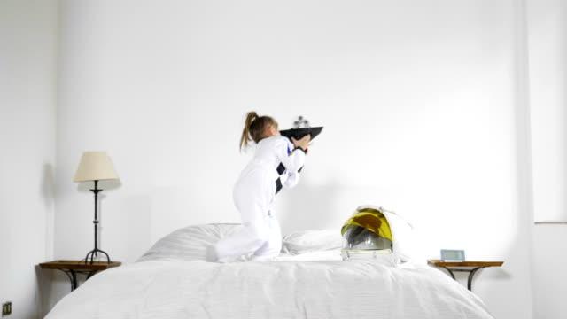 porträt eines mädchens gekleidet von astronauten mit shuttle spielen und beobachten die kamera lächeln. konzept: ehrgeiz, erfolg, kinder und ihre zukunft. - raumanzug stock-videos und b-roll-filmmaterial