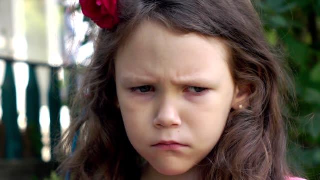 portrait of a little girl in a rural garden. slow motion - abbigliamento da neonato video stock e b–roll