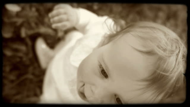 HD SLOW-MOTION: Portrait Of A Little Girl HD720p: SLOW-MOTION old fashion shot of a happy little girl sitting in the grass and looking up. Film look. sepia toned stock videos & royalty-free footage