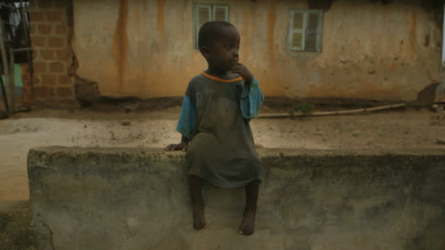 Portrait of a lonely small boy in African village Portrait of a poor and lonely small boy in an African village. He's sitting on a wall with a distant look on his face. A man is passing in the background a few seconds in the shot. poverty stock videos & royalty-free footage