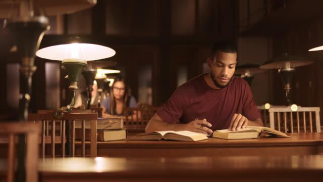 DS hombre africano-americano estudiante estudiando en la biblioteca - vídeo