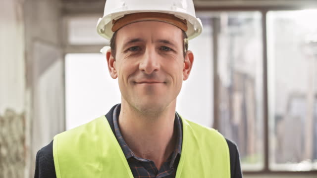 Portrait of a male construction manager holding the plans in his hand at the construction site video