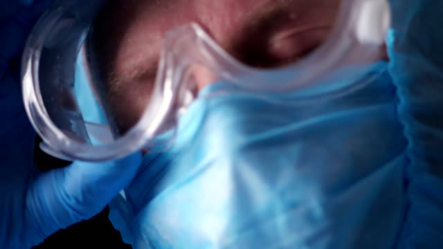 Portrait of a male medical worker. Exhausted and tired doctor taking off coronavirus protective uniform, mask, glasses and protective screen. a pandemic covid-19 - vídeo