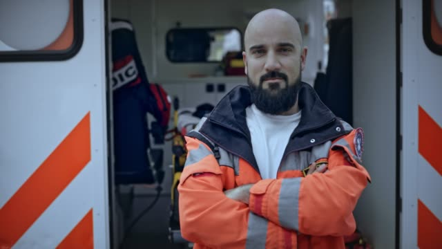 Portrait of a male paramedic with a beard standing next to the ambulance video