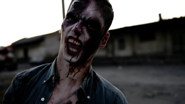 Portrait of a male zombie with bloody teeth and wounded face screaming and shouting. Halloween, filming, staging concept. Blurred abandoned town on the background Portrait of a male zombie with bloody teeth and wounded face screaming and shouting. Halloween, filming, staging concept. Blurred abandoned town on the background. vampire stock videos & royalty-free footage
