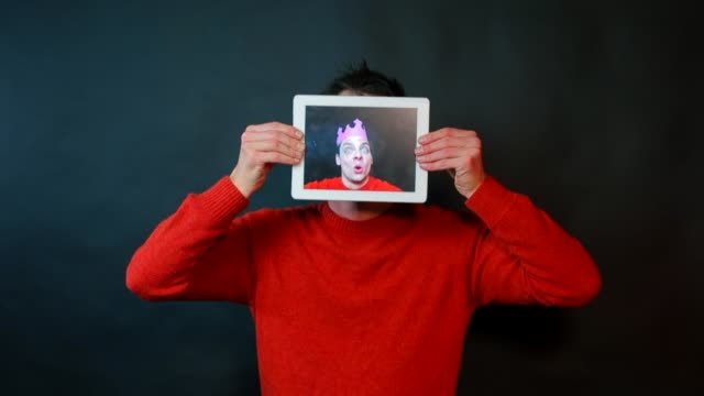 Portrait of a man on a tablet screen.