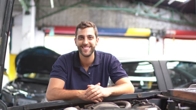 portrait of a man repairing a car in auto repair shop - mechanik filmów i materiałów b-roll