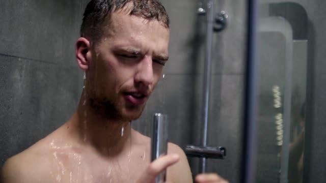 Porträt eines Mannes, die emotional singen unter der Dusche mit dem Duschkopf mit fließendem Wasser anstelle von einem Mikrofon – Video