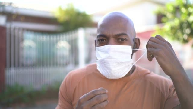 vídeos de stock e filmes b-roll de portrait of a man taking face mask off at street - remover