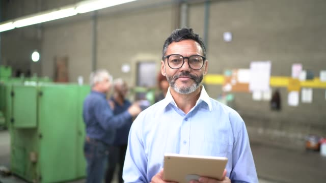 Portrait of a man using a digital tablet in the production line of a factory Portrait of a man using a digital tablet in the production line of a factory manufacturing occupation stock videos & royalty-free footage