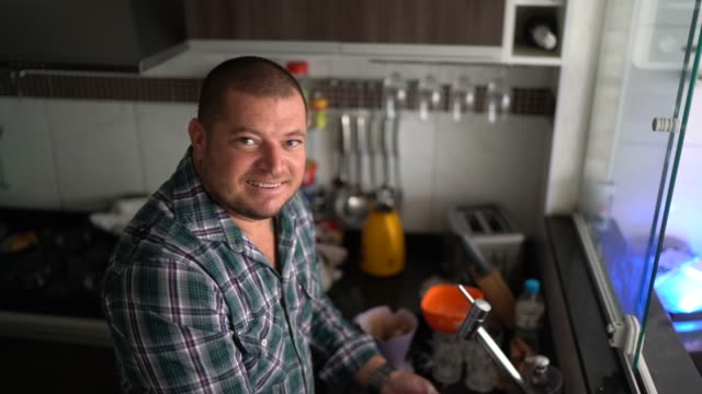 Portrait of a man washing dishes at home