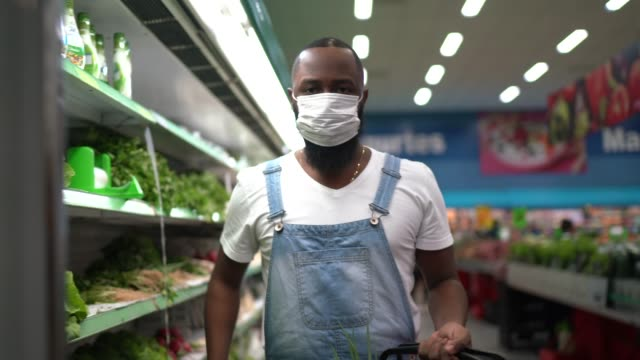 vídeos de stock e filmes b-roll de portrait of a man with disposable medical mask shopping in supermarket - afro latino mask