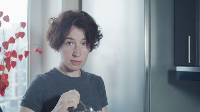 Portrait of a mature woman eating orange smoothie next to the fridge