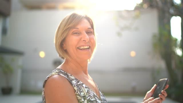 vídeos de stock, filmes e b-roll de retrato de uma mulher madura na frente de uma casa - brasileiro pardo