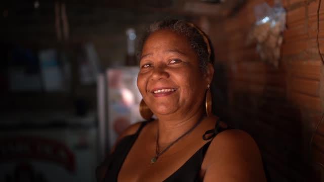 porträt einer reifen frau vor einem watt-und daumenhaus - brasilianischer abstammung stock-videos und b-roll-filmmaterial
