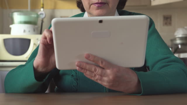 DOLLY: Portrait of a mature woman with a glasses uses a Tablet PC at home video