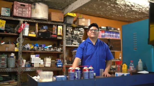 vídeos de stock, filmes e b-roll de retrato de um mecânico que trabalha em uma auto loja de reparo - pequeno