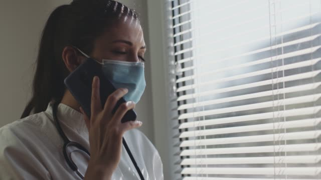 Portrait of a medical nurse talking on Smart Phone by the window - stock video