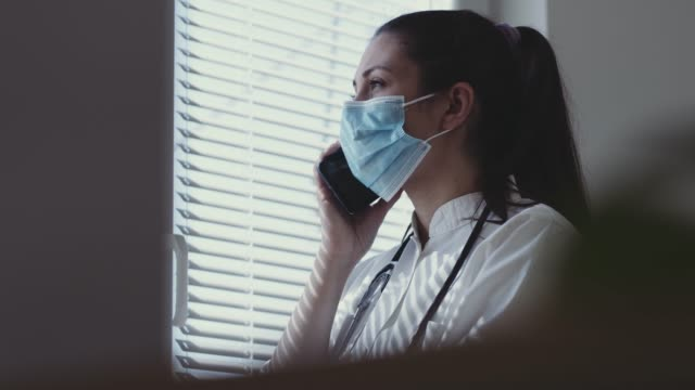 porträt einer krankenschwester, die auf dem handy am fenster spricht - stockvideo - smartphone mit corona app stock-videos und b-roll-filmmaterial