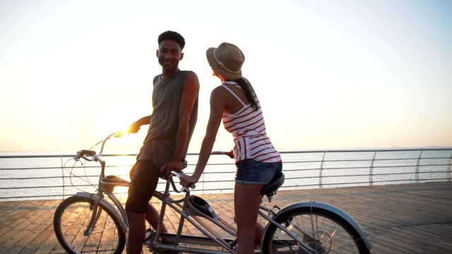Portrait of a mixed race couple riding on tandem bicycle outdoors near the sea, slow motion video