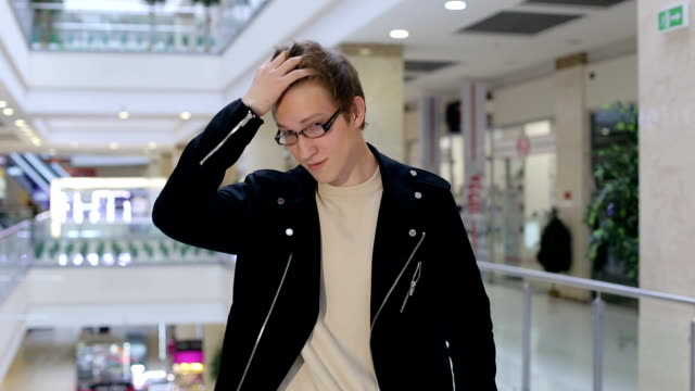 Portrait of a modern young man in glasses in a large shopping center. Shopping.