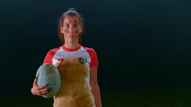 slo mo portrait of a muddy female rugby player holding a ball - trykot filmów i materiałów b-roll