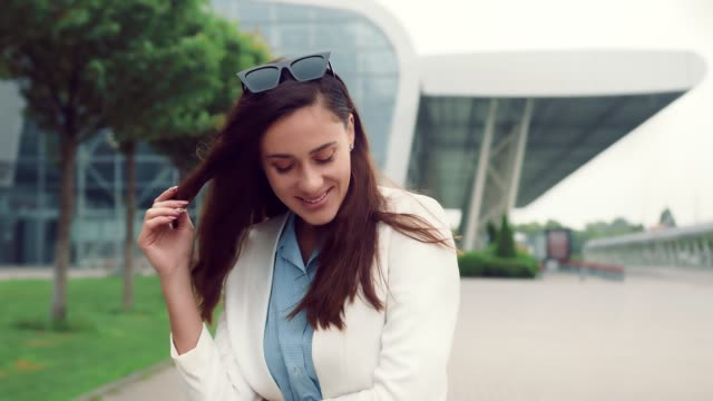 porträt einer hübschen kaukasischen frau mit schwarzen haaren lächelnd und mit blick auf die kamera. mädchen auf der straße auf einem hintergrund von modernen interieurs lächelnd in die kamera. - weibliche führungskraft stock-videos und b-roll-filmmaterial