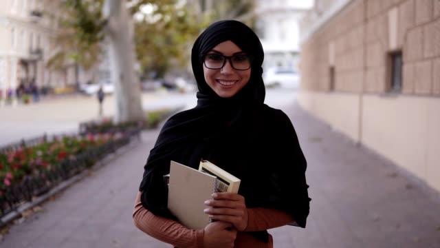 Porträt einer hübschen muslimischen Frau in einem schwarz gefärbten traditionellen Kopftuch. Muslimische Studentin steht zurück zu ihrem College oder ihrer Universität, hält Bücher in der Hand und lächelt in die Kamera – Video