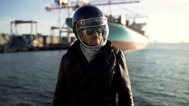 portrait of a professional rider or motorcyclist, in a protective black helmet - campionato video stock e b–roll